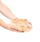 Hands holding round bread. Royalty Free Stock Photography