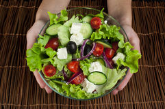 Hands holding salad in a glass bowl Royalty Free Stock Photo