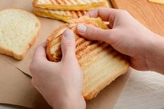Hands holding a sandwich. Just from a panini press. Crunchy bread with striped grill marks and melted cheese royalty free stock photo