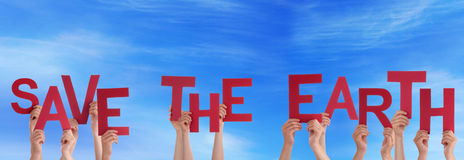 Hands Holding Save The Earth in the Sky. Many Hands Holding the Red Words Save The Earth in the Sky Stock Photos