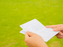Hands holding saving account passbook. Book bank on the green grass background Stock Images