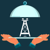 Hands holding a serving dish with the oil rig. Investment in mineral extraction royalty free illustration