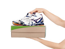 Hands holding shoes in a box Stock Photography