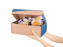 Hands holding shoes in a box Stock Image