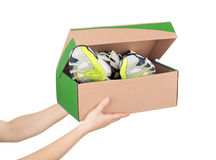 Hands holding shoes in a box Royalty Free Stock Images