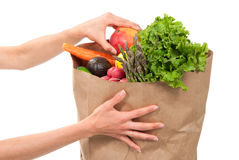 Hands holding shopping paper bag full of groceries. Hands holding a shopping paper bag full of groceries, one hand pick out ripe mango, avocado, asparagus Royalty Free Stock Photos