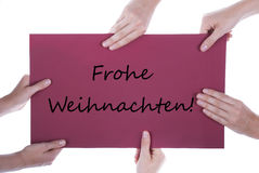 Hands Holding Sign Frohe Weihnachten. Many Hands Holding a Red Sign togehter with the German Words Frohe Weihnachten which means Merry Christmas royalty free stock photo
