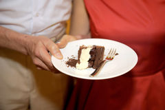 Wedding Chocolate Cake. Hands holding slice of wedding chocolate cake Stock Photos