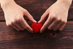 Hands holding small bright red heart Royalty Free Stock Photo
