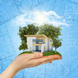 Hands holding a small house with land Stock Image