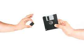 Hands Holding Small Memory Card Versus Old Floppy Disk Royalty Free Stock Image