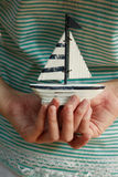 Hands holding small saiboat. Two hands holding a small sailboat Royalty Free Stock Images