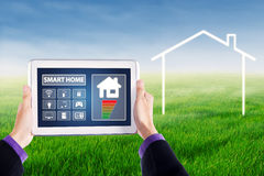 Hands holding smart house controller at field Royalty Free Stock Photo