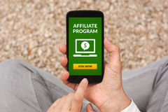 Hands holding smart phone with affiliate program concept on scre. En. All screen content is designed by me. Flat lay Royalty Free Stock Images