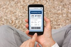 Hands holding smart phone with boarding pass concept on screen. All screen content is designed by me. Flat lay royalty free stock photo