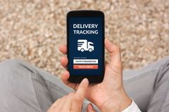 Hands holding smart phone with delivery tracking concept on scre. En. All screen content is designed by me. Flat lay Royalty Free Stock Photo
