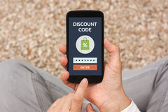 Hands holding smart phone with discount code concept on screen. All screen content is designed by me Royalty Free Stock Image