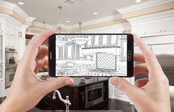 Hands Holding Smart Phone Displaying Drawing of Kitchen Photo Be Royalty Free Stock Photo