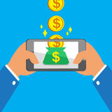 Hands holding smart phone earning big coins to money bag Stock Photo