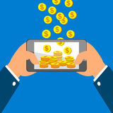 Hands holding smart phone and Earning Coins Stock Photo