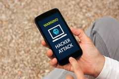Hands holding smart phone with hacker attack concept on screen Stock Images