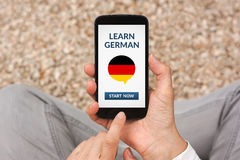 Hands holding smart phone with learn german concept on screen Stock Images