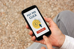 Hands holding smart phone with Pay Per Click concept on screen. Hands holding smart phone with Pay Per Click PPC concept on screen. All screen content is royalty free stock images