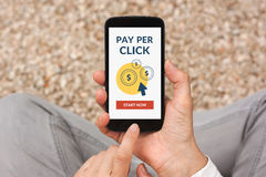 Hands holding smart phone with Pay Per Click concept on screen. Hands holding smart phone with Pay Per Click PPC concept on screen. All screen content is stock photo