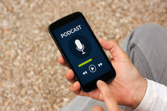 Hands holding smart phone with podcast concept on screen Stock Image