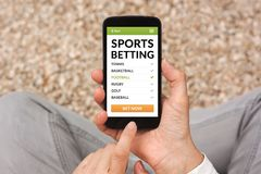 Hands holding smart phone with sports betting concept on screen. All screen content is designed by me. Flat lay royalty free stock image