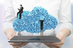 Hands holding smart tablet.  Businessmen teamwork blue characters cloud shape stock photography