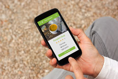 Hands holding smartphone with food application mock up on screen Stock Photography