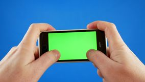 Hands holding the smartphone and play the game. Smartphone on blue background with green screen chromakey. Game concept stock video