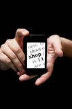 Hands Holding Smartphone, showing the word Shop printed stock photography