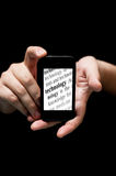 Hands Holding Smartphone, showing the word Technology printed stock photo