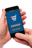 Hands holding smartphone with signs click and collect or home delivery Stock Photography