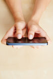 Hands holding smartphone on table Royalty Free Stock Image