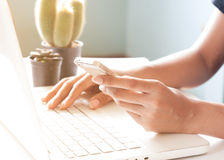 Hands holding smartphone and using laptop. Online Stock Images