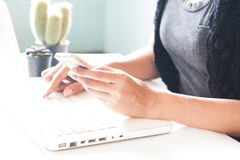 Hands holding smartphone and using laptop. Online Royalty Free Stock Images