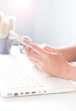 Hands holding smartphone and using laptop. Online Royalty Free Stock Photo