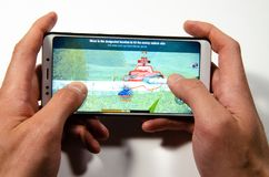 Hands holding a smartphone on which the game, gameplay Gameplay World of Tanks Blitz royalty free stock images