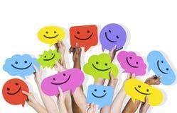 Hands Holding Smiley Face Speech Bubbles