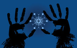 Hands holding a snowflake on a blue background Stock Image