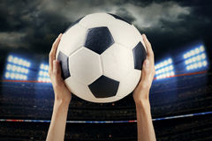 Hands holding soccer ball at stadium Royalty Free Stock Photo