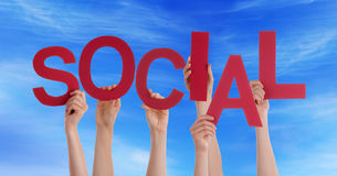 Hands Holding Social in the Sky. Many Hands Holding the Red Word Social in the Sky Royalty Free Stock Images