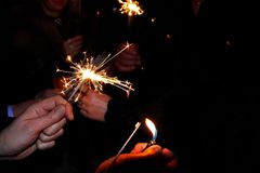 Hands holding sparklers. People lit the sparklers under the chiming clock for the new year royalty free stock image