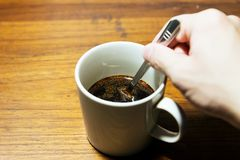 Hands holding spoon with a cup of coffee on rustic wooden table. Background - Top view with copy space royalty free stock photos