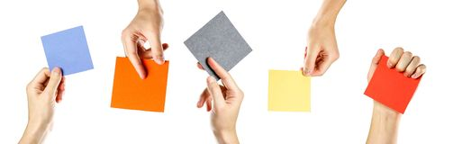 Hands holding square blank colored paper. Close up. Isolated on stock photo