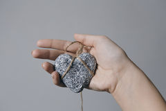 Hands holding a stone heart in jute bondage against grey background. Valentine`s day concept, horizontal view royalty free stock images