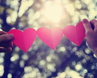 Hands holding a string of paper hearts up to the sun Royalty Free Stock Image